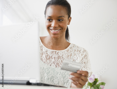 Black woman shopping online with credit card