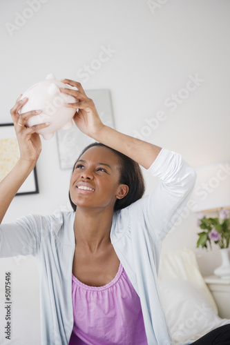Black woman trying to get money out of piggy bank