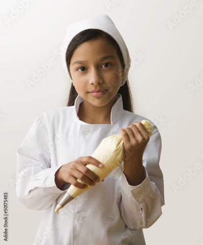 Hispanic girl holding frosting bag