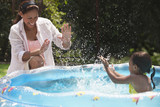 Hispanic girl in kiddie pool splashing mother