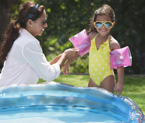 Hispanic mother putting floaties on daughter