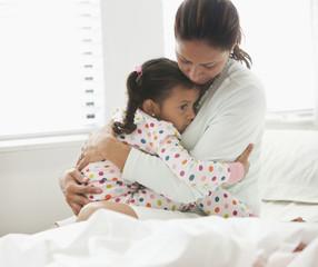 Hispanic mother comforting daughter