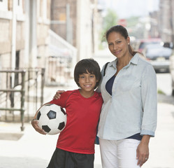 Hispanic boy with soccer ball hugging mother