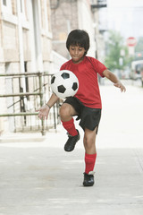Hispanic boy practicing with soccer ball on city sidewalk