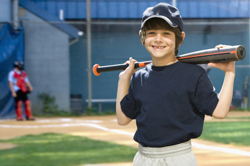 Caucasian boy holding baseball bat on field