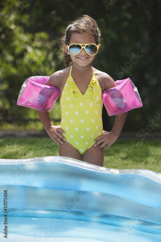 Hispanic girl standing near kiddie pool