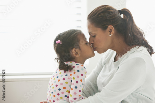 Hispanic mother kissing daughter