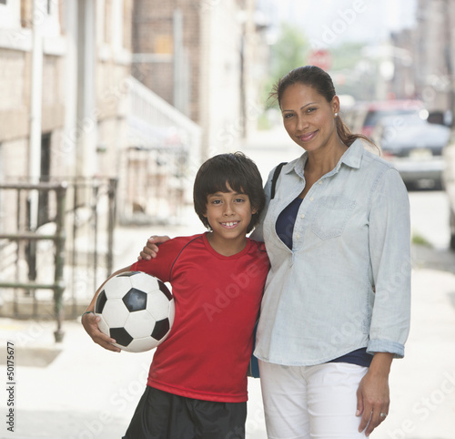 Hispanic boy with soccer ball hugging mother