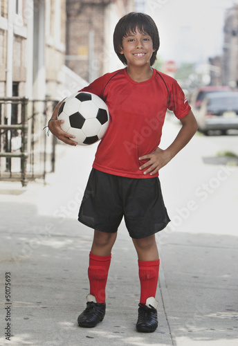 Hispanic boy holding soccer ball on city sidewalk