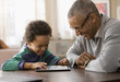 Grandfather and grandson using digital tablet together