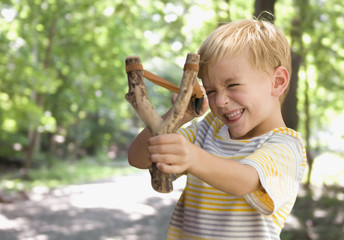 Caucasian boy shooting slingshot