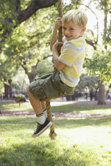 Caucasian boy swinging on rope swing