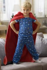 Caucasian boy in superhero costume standing on sofa