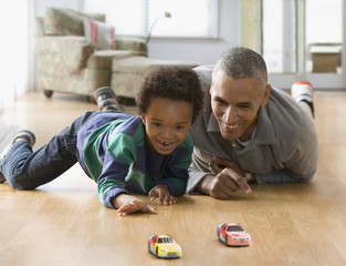 Grandfather and grandson playing with toy cars