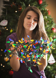 Caucasian woman holding tangled Christmas lights