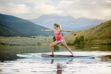Caucasian woman practicing yoga on paddle board