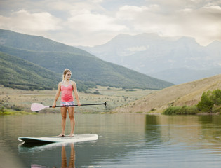 Caucasian woman on stand up paddle board