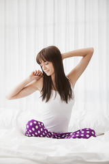 Caucasian woman sitting on bed stretching