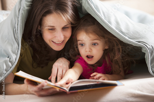 Caucasian mother and daughter reading book under covers