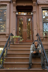 Black man sitting on front stoop using digital tablet
