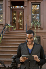 Smiling Black man using digital tablet