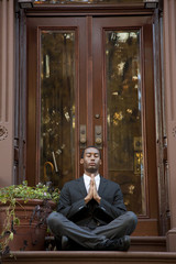 Black businessman practicing yoga on front stoop