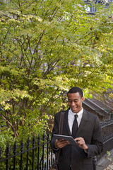 Black businessman using digital tablet outdoors