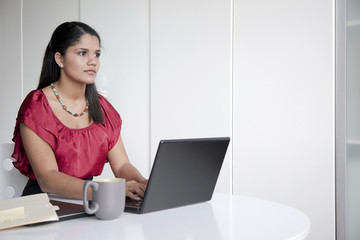 Hispanic businesswoman typing on laptop in office