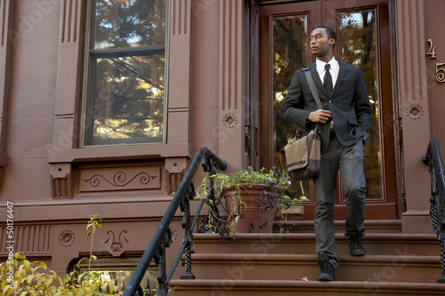 Black businessman walking down front stoop steps