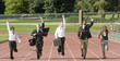 Business people running across track finish line
