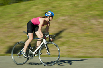Caucasian woman riding bicycle in park