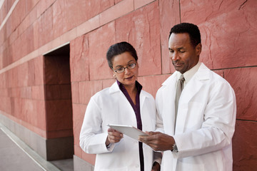Doctors using digital tablet outdoors
