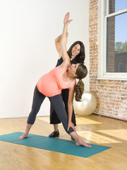 Pregnant Caucasian woman working with personal trainer