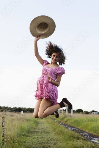 Excited girl jumping in field
