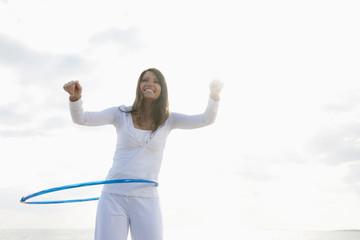 Hispanic woman playing with hula hoop