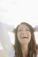 Laughing Hispanic woman with head in hands