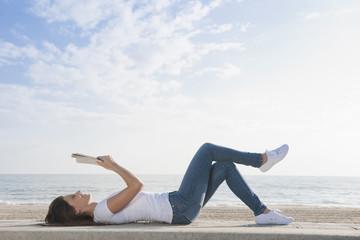 Hispanic woman reading book on beach