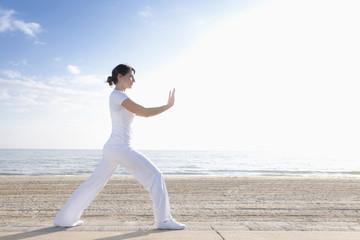 Hispanic woman practicing yoga on beach