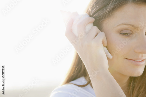 Hispanic woman listening to seashell