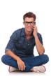 man sitts & speaks on phone