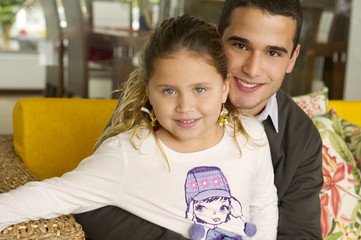 Hispanic girl sitting on father's lap