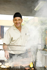 Hispanic man cooking food on barbecue grill