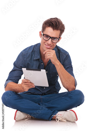 seated man holds a tablet