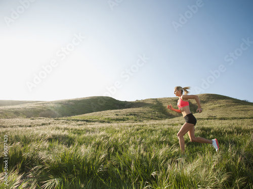 Caucasian woman running in remote field