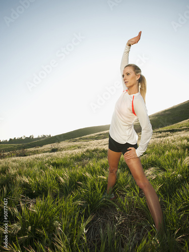 Caucasian woman stretching in remote field