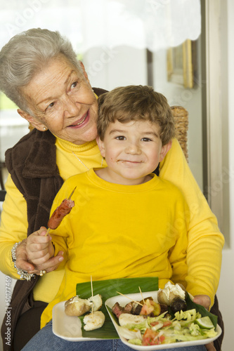 Hispanic boy eating while sitting on grandmother's lap