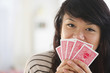 Pacific Islander woman covering her mouth with playing cards
