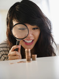 Pacific Islander woman examining pennies with magnifying glass