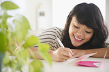 Pacific Islander woman writing on greeting card