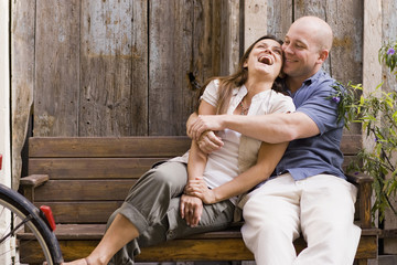 Laughing couple hugging on bench